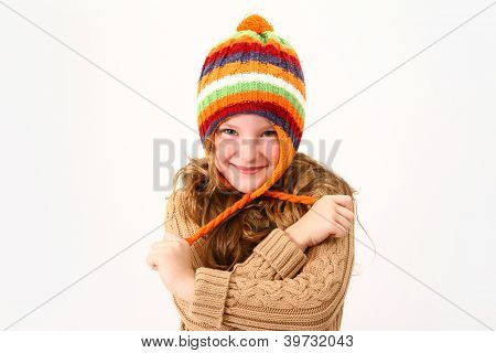 Cheerful Little Girl In Colorful Sweater And Hat Isolated On White Background
