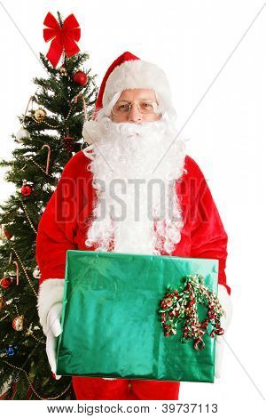 Santa Claus standing by the Christmas tree holding a shiny present.  White background.