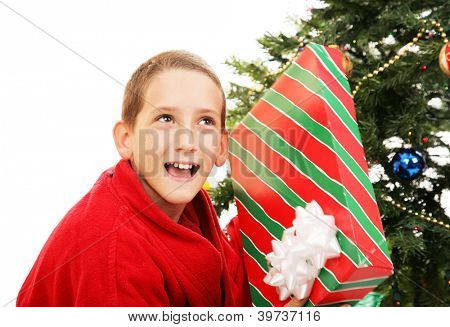 Cute little boy shaking a Christmas gift to guess what's inside.  White background.
