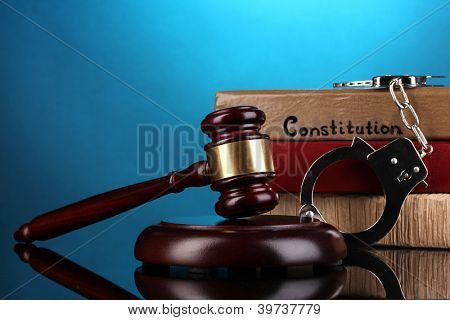 Gavel, handcuffs and books on law on blue background