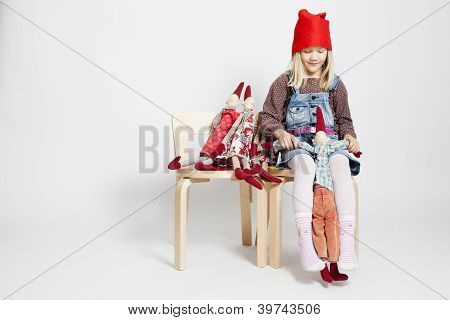 Happy Young Girl Playing With Toy Christmas Elf Dolls