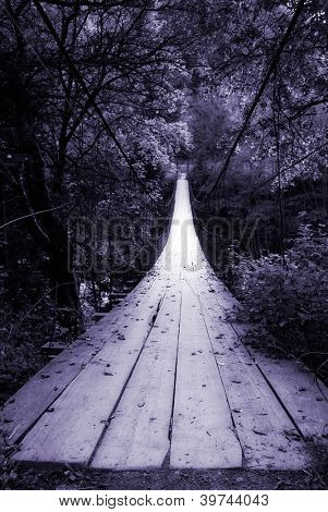 suspended wooden bridge illuminated by light