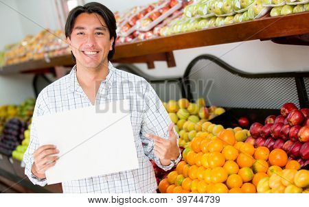 Man with an open sign at his grocery business