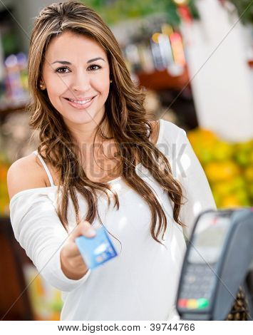 Woman at the checkout paying by credit card