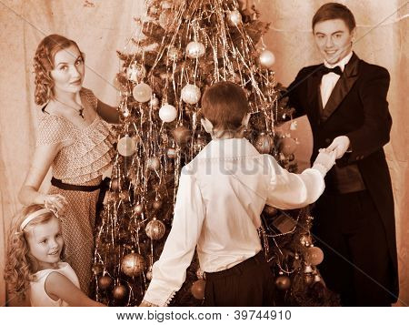 Happy family with children round dance  Christmas tree. Black and white retro.