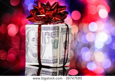 gift box made of dollars on blurred background