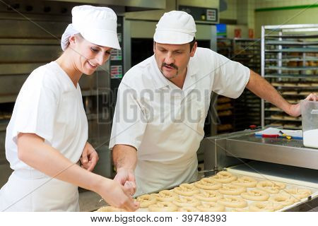 Female and male baker baking fresh bread in the bakehouse, they produce brezn