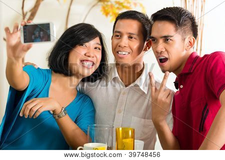 Amigos de Asia, dos hombres y una mujer, tener diversión tomando fotos con el teléfono móvil