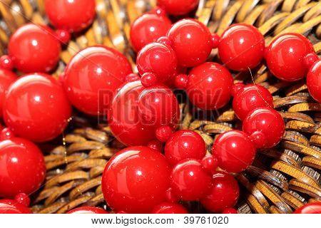 Red Necklace Over Brown Basket Background