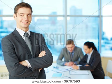 Image of cross-armed leader looking at camera in working environment
