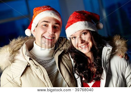 Portrait of happy couple in Santa caps looking at camera with smiles