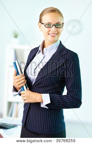 Portrait of elegant businesswoman with handbooks looking at camera with smile