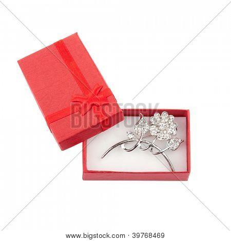 Hermoso broche de plata en una caja de regalo roja, aislado en blanco