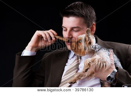 Young businessman sitting on the sofa with a cigar and a dog