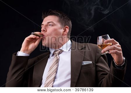 Businessman with an alcoholic drink and a cigar