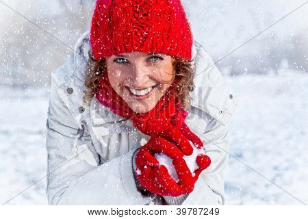 Happy young woman playing snowball fight on the snow day. Winter concept.