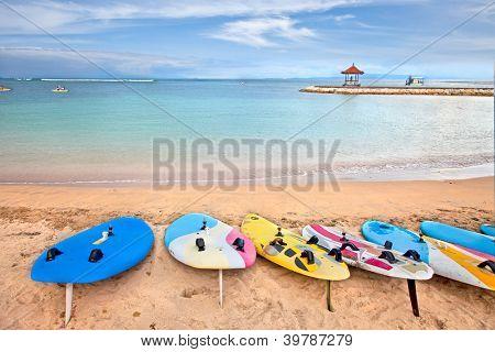 Surf boards on idyllic tropical sand Nusa Dua beach, Bali, Indonesia.