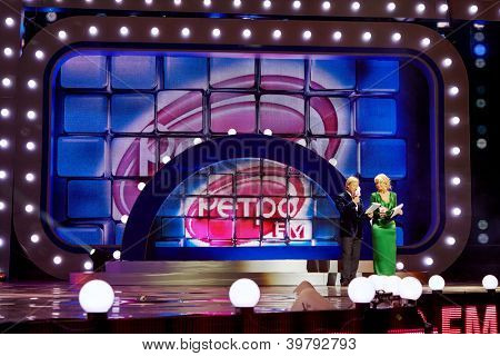 MOSCOW - DEC 17: Presenters of festival Dmitry Kharatyan and Tatyana Vedeneeva on stage in concert Legends of Retro FM in Sports Complex Olimpiyskiy, Dec 17, 2011, Moscow, Russia.
