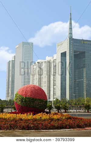 GUANGZHOU - NOV 23: Street flowerbed against skyscrapers, Nov 23, 2011, Guangzhou, Guangdong, China. GRCB is previously known as Guangzhou Rural Credit Cooperatives established in 1951.