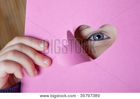Child looking through a heart shape card