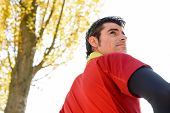 pic of breather  - Male athlete standing with towel around his neck and looking over his shoulder - JPG