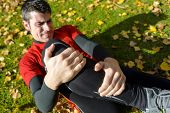 stock photo of fracture  - Male athlete lying on the ground and suffering a tibia fracture - JPG