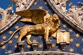 stock photo of building relief  - The Golden winged Lion of St Mark and book of justice on St Marks Basilica in the Italian city of Venice - JPG
