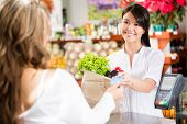 image of debit card  - Shopping woman at the checkout paying by card - JPG