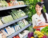 stock photo of local shop  - Woman at the supermarket with a shopping list - JPG