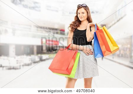 Satisfied young woman posing with shopping bags in a shopping center