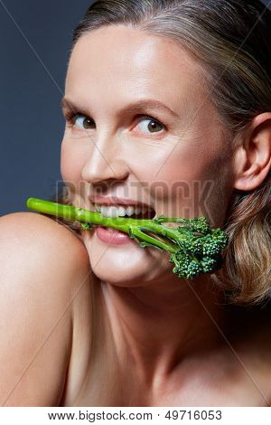 beautiful fourty year old woman with natural makeup and healthy skin texture on blue gray studio background holding a broccoli in her mouth