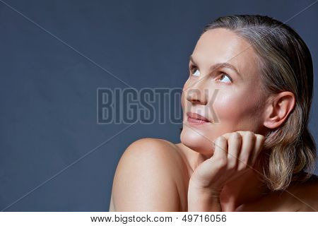 beautiful fourty year old woman with natural makeup and healthy skin texture on blue gray studio background with space for text