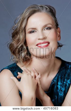 beautiful fourty year old woman with fashion makeup, curly hairstyle on grey blue studio background. Wearing green velvet dress