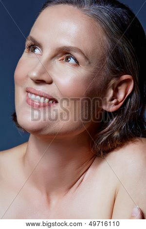 beautiful fourty year old woman with natural makeup and healthy skin texture on blue gray studio background