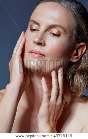 beautiful fourty year old woman with natural makeup and healthy skin texture touching her face on blue gray studio background