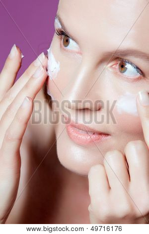 beautiful fourty year old woman with natural makeup and healthy skin texture on pink studio background with cream on her face