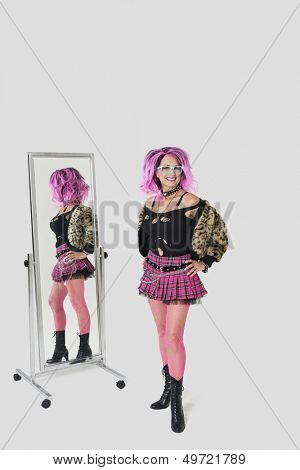 Portrait of senior female punk standing by mirror over gray background