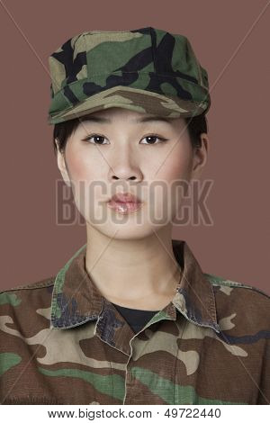 Portrait of beautiful young US Marine Corps soldier in camouflage clothing over brown background