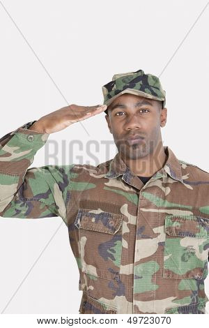 Portrait of an African American US Marine Corps soldier saluting over gray background