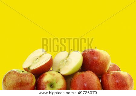Bunch of fresh Braeburn apples and a cut one  on a yellow background with copy space