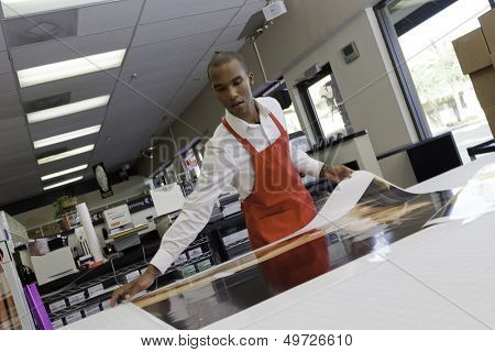 Manual worker taking large printouts