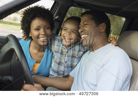 Cheerful little boy and parents sitting in car