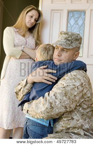 Loving soldier embracing son before departing while mother looking at them