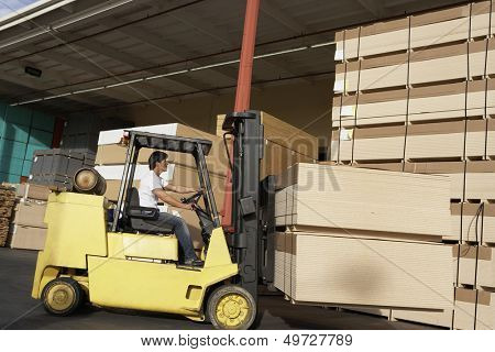 Side view of manual worker operating a forklift truck in lumber industry