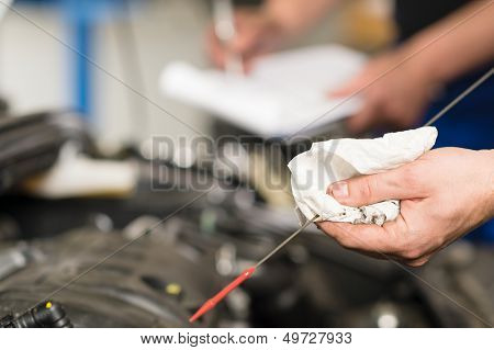 Closeup of the hand of car mechanic checking oil