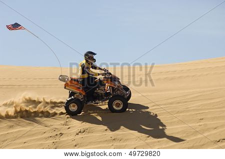 Side view of young man riding quad bike in desert