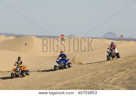 Three men riding quad bikes in desert