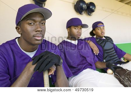 Portrait of baseball players sitting in dugout