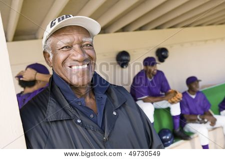 Portrait of senior coach smiling with players in background