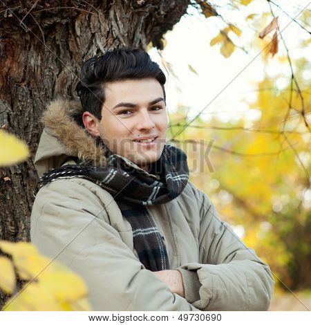 Young smiling man portrait standing in front of an autumn tree.